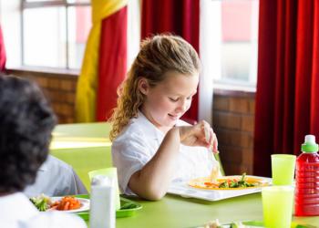 Smiling schoolgirl having food with classmates in canteen