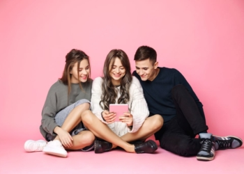 Young beautiful friends smiling looking at tablet over pink background. Copy space.